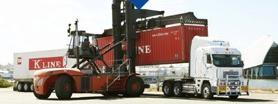 container being loaded onto freight truck