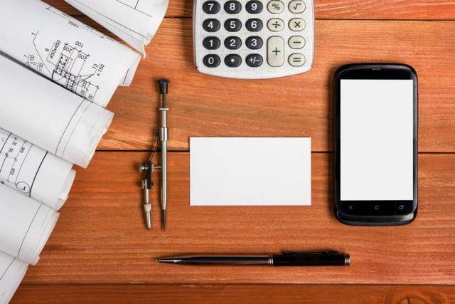 tavolo con compasso, penna smartphone, calcolatrice e fogli