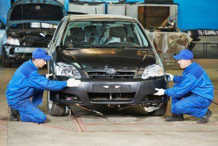 Due meccanici fissando le parti dell'automobile