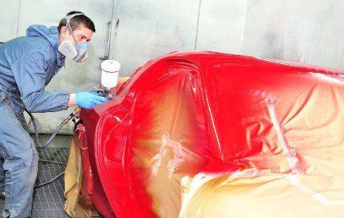 Operaio dipingendo un'auto di colore rosso