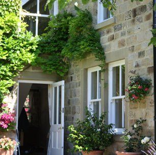 Climbing ivy over white front door in stone building