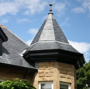 A pointed grey roof with weather vane