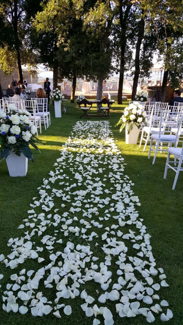 delle panchine e un altare di una chiesa decorata con dei fiori bianchi