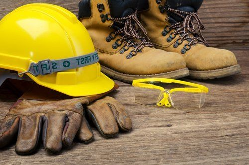guanti, casco, occhiali e scarpe antinfortunistica su tavola di legno