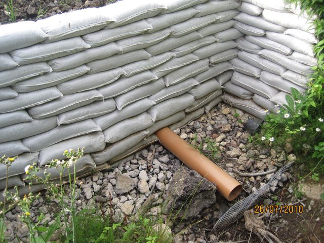 sandbag wall with drainage pump pipe beneath