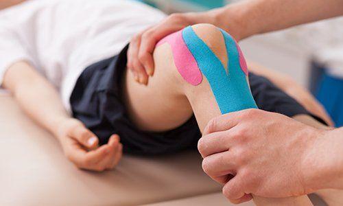 una fisioterapista che controlla un ginocchio con delle fascie elastiche