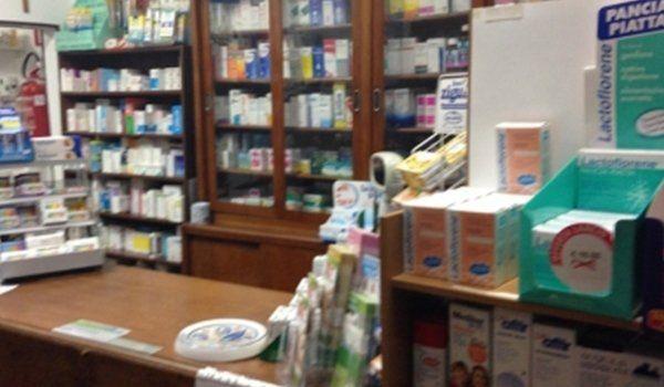 vista del bancone della farmacia e di un armadio vetrina con dei prodotti farmaceutici