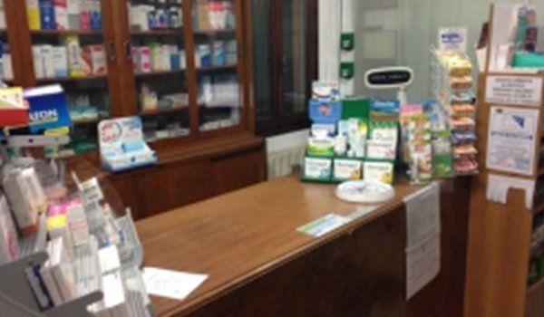 il bancone in legno della farmacia con prodotti in esposizione