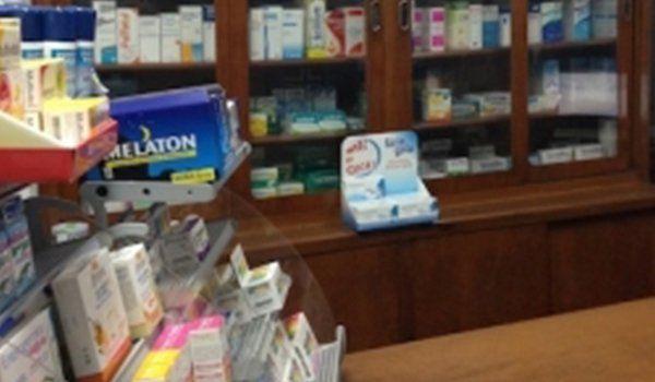 una vetrinetta sulla sinistra con farmaci e prodotti omeopatici e di fronte un armadio in legno e vetro con altri prodotti