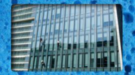 addetti specializzati puliscono facciata esterna in vetro di un edificio