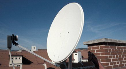 A large white satellite dish on a roof