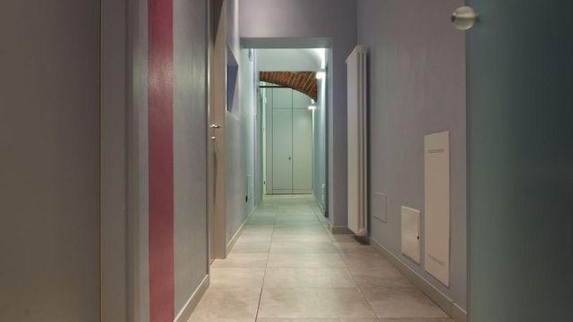 Corridoio dello studio dentistico dove vediamo mezzo arco di mattoni