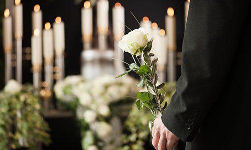 un uomo con una rosa in mano davanti e delle candele bianche accese