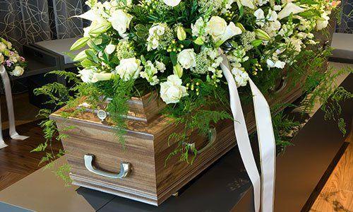 una bara con delle rose bianche sopra