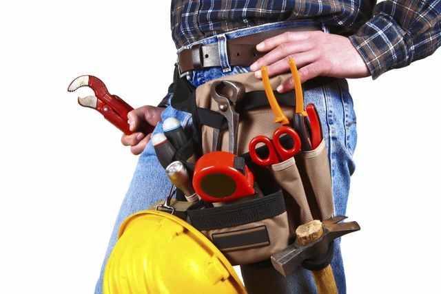 worker with toolbelt to provide water heater services in Show Low, AZ