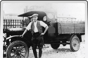 Old black and white photo of a man standing in front of an old pickup truck