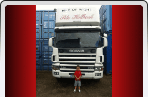 Young boy standing in front of a Pete Holbrook Removals lorry