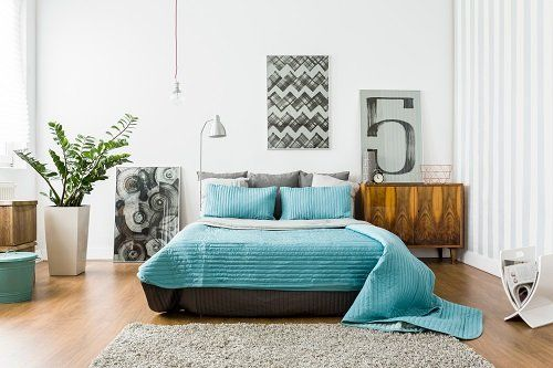 Camera da letto in toni turchese e grigie con tabelle moderni e una pianta
