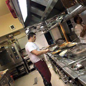 Cuoco lavorando in una cucina ampia
