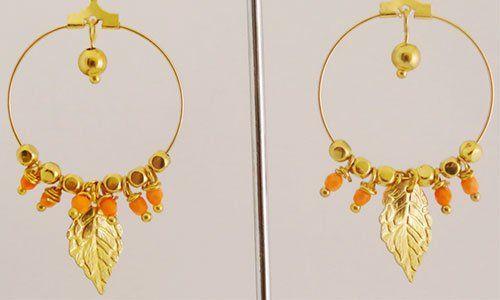 due orecchini dorati con una foglia come pendente