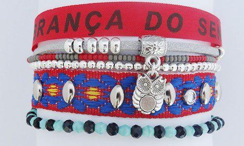 un bracciale di color rosso e blu con degli oggetti argentati