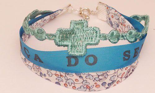 un bracciale azzurro con un ricamo di una croce color turchese e disegni a fiori blu su sfondo rosa