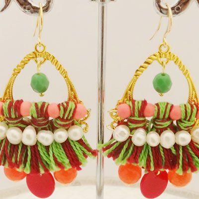 due orecchini con delle frangette verdi e rosse che pendono e delle perline