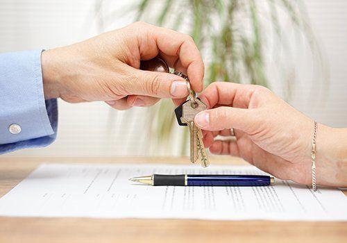le mani di un uomo checonsegna delle chiavi di casa nelle mani di una donna
