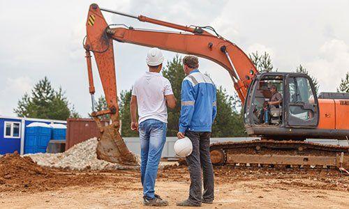 Due costruttori con casco, rivolto indietro, guardando l'escavatore