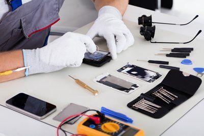 addetto con guanti bianchi mentre ripara uno smartphone