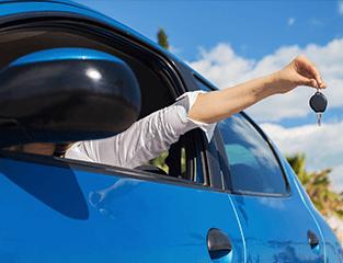 una mano con una chiave fuori da un finestrino di un'automobile