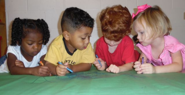 Teacher communicating with children at our center in Foley, AL
