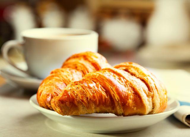 colazione con croissant, tazza di caffè nero e giornale