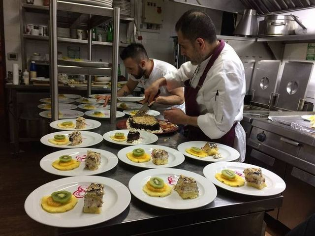 cuochi in cucina preparano dei piatti con dessert