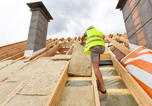 operaio mentre installa materiale di isolamento su un tetto sulla nuova casa in costruzione