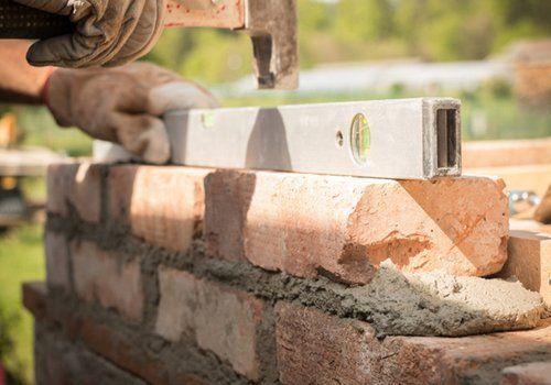 muratore che costruisce un muro di mattoni