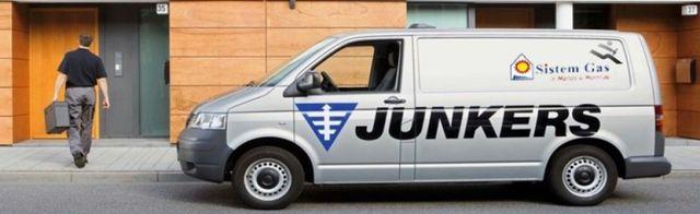 un furgone con scritto  Sistem Gas Junkers e un tecnico che entra in una casa