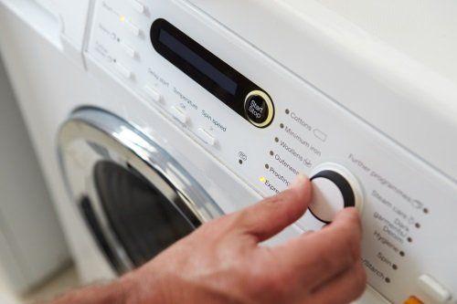 Mano che programma una lavatrice