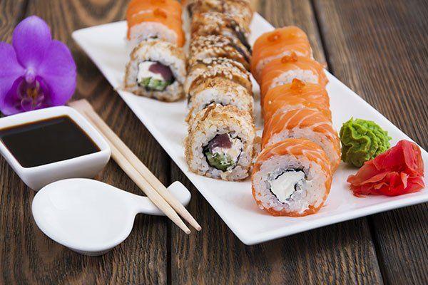 un vassoio con vari tipi di sushi e accanto salsa di soia