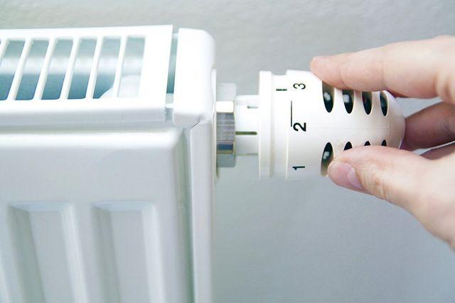 una mano sta regolando una valvola di un termosifone