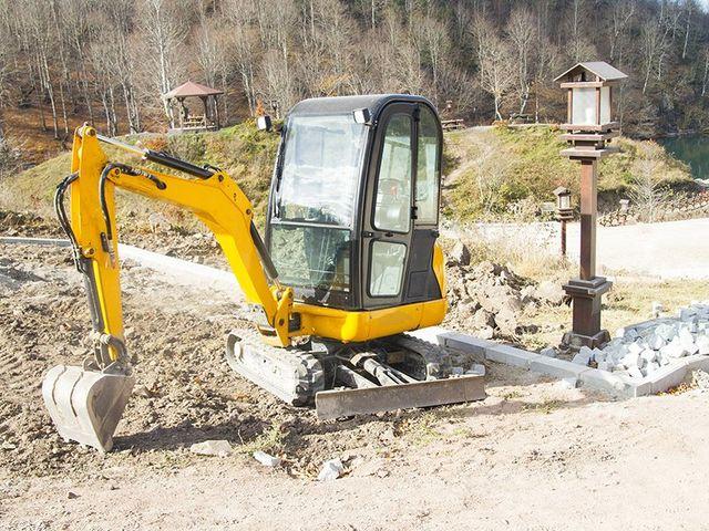 una scavatrice gialla al lavoro in un terreno