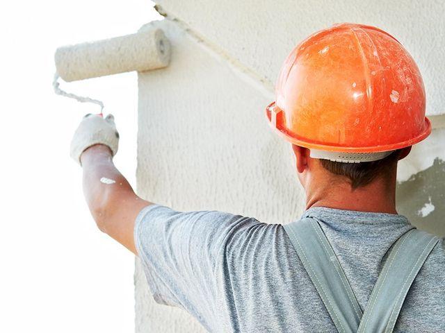 un imbianchino con un caschetto arancione mentre imbianca un muro con un rullo