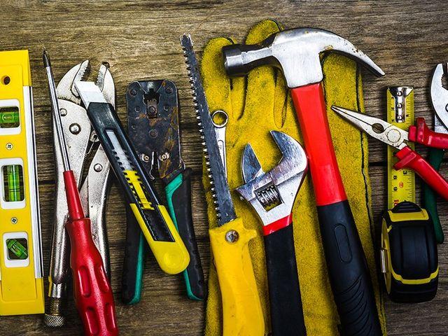 livella,cacciavite,pinza cromata,taglierino, martello e altri attrezzi appoggiati su un banco da lavoro in legno
