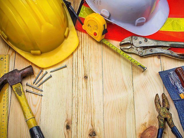 degli elmetti e degli attrezzi da lavoro su un tavolo di legno