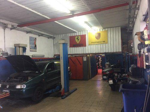 Interno dell'officina meccanica con un'auto e gli strumenti del meccanico