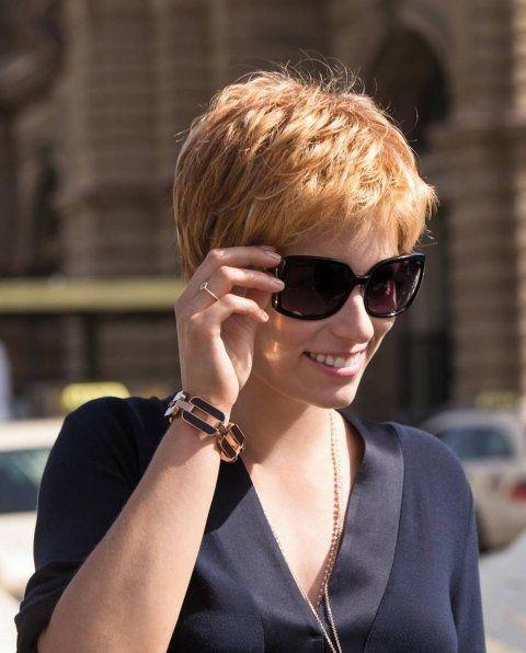 una donna con gli occhiali da sole e i capelli corti biondi