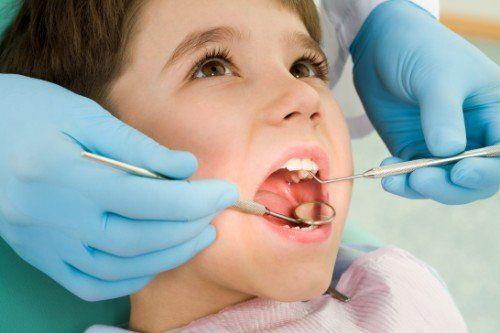 Il dentista che visita la bocca di un bambino con lo specchio