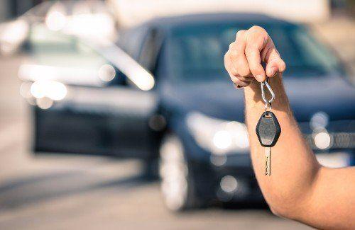 una mano sostiene un paio di chiavi, sullo sfondo un'auto
