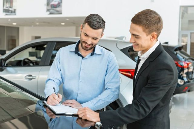 Young male consultant and buyer signing contract for new car in auto show