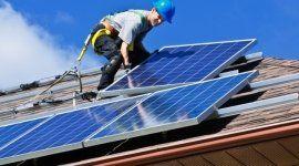 operaio che monta un pannello solare su un tetto